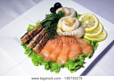 Mixed meat - fish cold cut on a white glass plate