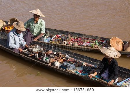 INLE LAKE MYANMAR - JANUARY 14 2016 : Unidentified Burmese people on small long wooden boat selling souvenirs trinkets and bijouterieat the floating market on Inle Lake Myanmar