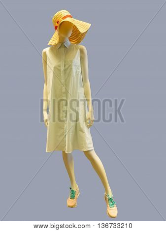 Female mannequin wearing summer dress and straw hat against grey background. No brand names or copyright objects.