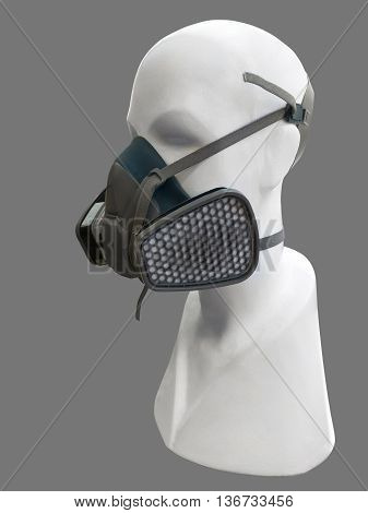 Mannequin wearing protective dust mask with valve over gray background.