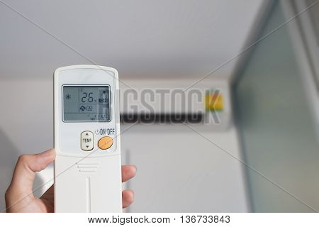 Left hand holding remote air conditioner turn up to 26 celcius with air conditioner blurred background