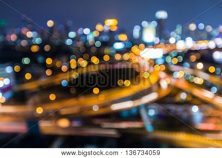 Night blurred bokeh lights city downtown and interchanged at twilight, abstract background
