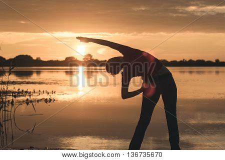 young slim woman doing exercises on the shore of the lake at sunset