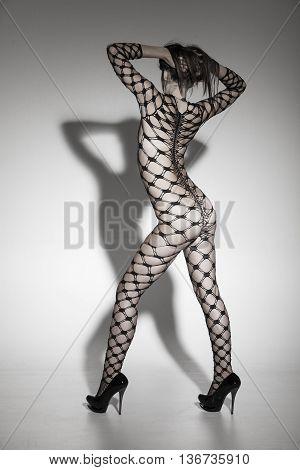 slim woman in a bodysuit throwing a shadow