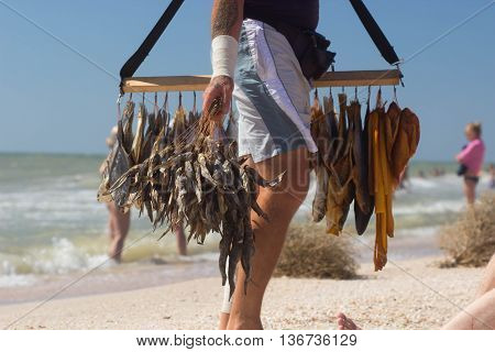 Funny original merchants sell dried and smoked fish with beer on beach with tourists, selling beer and shrimp. Petty trade on open public beach. Local popular services.