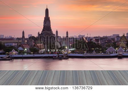 Opening wooden floor, Arun temple water front, the most famous landmark of Thailand during sunset