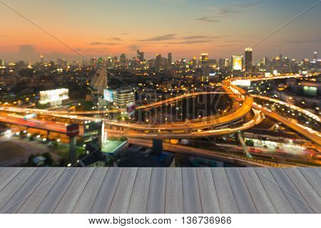 Opening wooden floor, Aerial view burred light city interchanged road and office building background during sunset