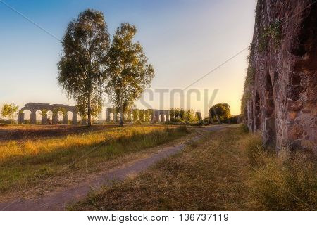 A country lane runs along the mighty walls of an ancient Roman aqueduct. To the right another aqueduct against the background of the sunset.