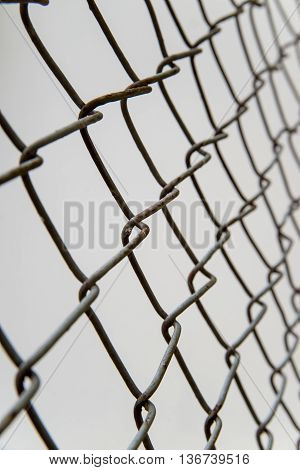 Chain-link fence at an angle on a gray background. Immigration and security concept.