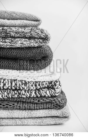 Pile of knitted winter clothes on wooden background, sweaters, knitwear, space for text black and white