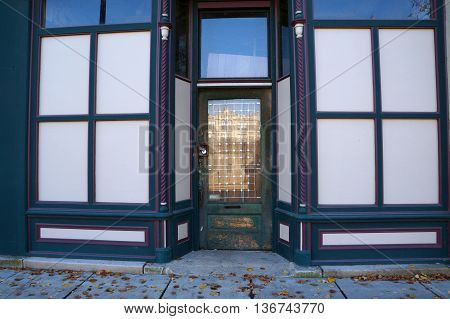 The front door of a vacant building with boarded-up store windows in downtown Joliet, Illinois.