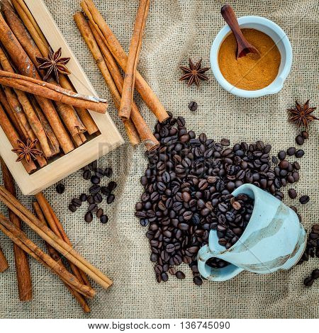 The Cup Of Coffee Beans On The Cloth Sack With Cinnamon Sticks ,cinnamon Powder In The Bowl And Star