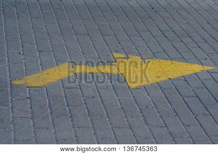 Yellow traffic arrow on cobblestone pavement, street sign