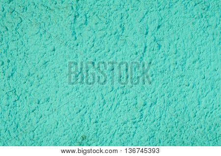 Background of a turquoise blue stucco coated and painted exterior rough cast of cement and concrete wall texture decorative coating