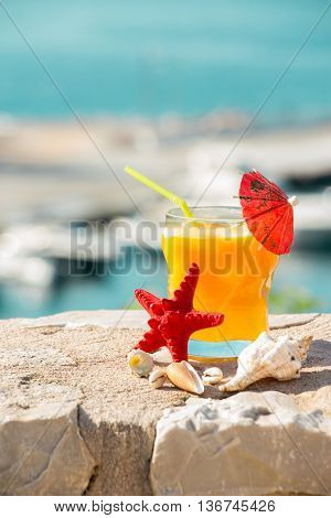 Right a glass of fresh orange juice next to shells to the left the empty space on the background of the sea. Orange juice sea and seashells. Vertical. Daylight.