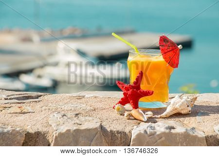 Right a glass of fresh orange juice next to shells to the left the empty space on the background of the sea. Orange juice sea and seashells. Horizontal. Daylight.