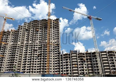 New high-rise modern apartment buildings, construction in process, during bright sunny day, front view horizontal
