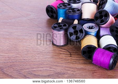 Scattered Cotton Reels On A Wooden Surface