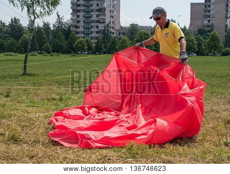 Saint-Petersburg Russia - June 26 2016: Kite Festival in the town of Pushkin. Man preparing to launch a red kite.