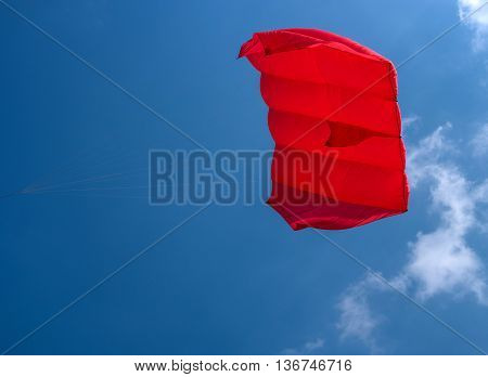 Red kite flying against a blue sky. Snake launched at the festival of kites in Pushkin.