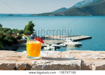 Left a glass of fresh orange juice next to shells to the right the empty space on the background of the sea. Orange juice sea and seashells. Horizontal. Daylight.
