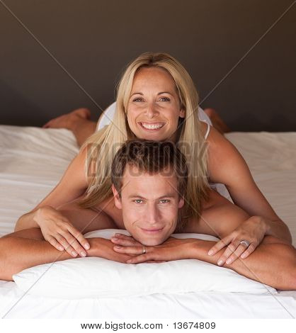 Beautiful woman on a mans back in bed having fun