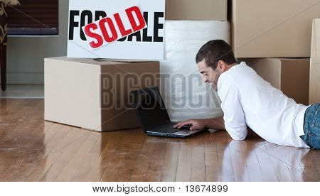 Young adult male using a laptop on the living room floor