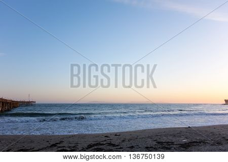 Breezy evening surf at Ventura city beach near historic wooden pear with a distant chain of Channel Islands California