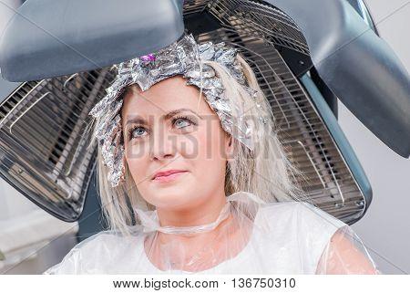 Beauty Salon. Caucasian Woman Under Hair Dryer Awaiting Next Step of Hair Styling.