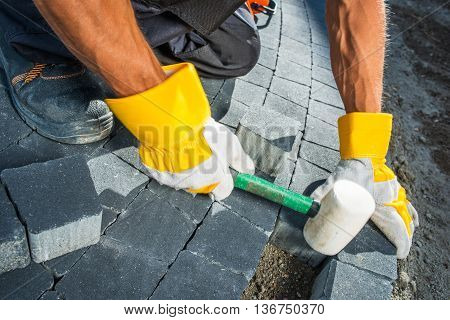 Cobble Brick Paving Works. Men Paving Garden Path using Bricks Closeup Photo.