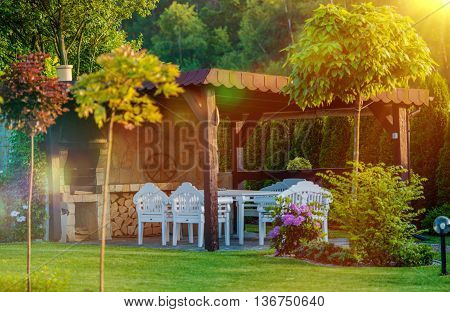 Outdoor Garden BBQ Area. Garden Grilling Place with Fireplace and White Garden Furnitures.