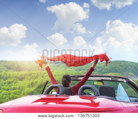 Girl in a red convertible car on a background seascape with a shawl waving in the wind.