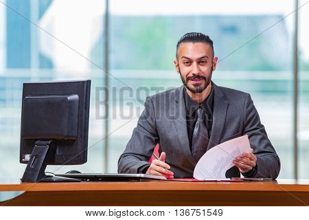 Happy businessman sitting at the desk