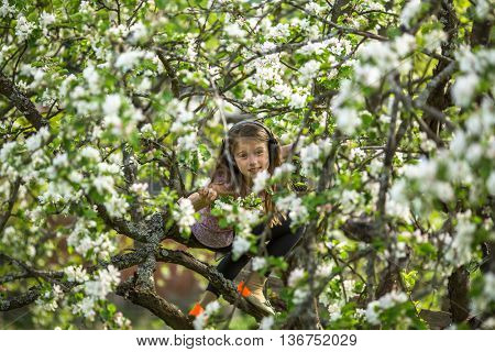 Little girl hid in the branches of a blossoming Apple tree.