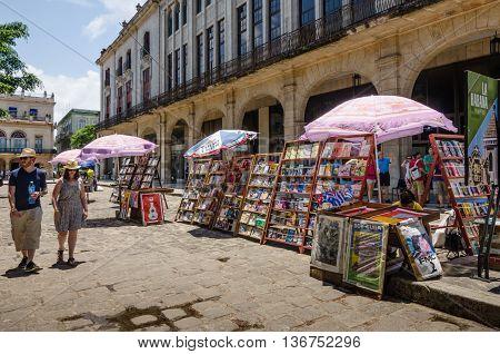 HAVANA - CUBA JUNE 13, 2016: Tourists walk by book and magazine stalls at Plaza de Armas.