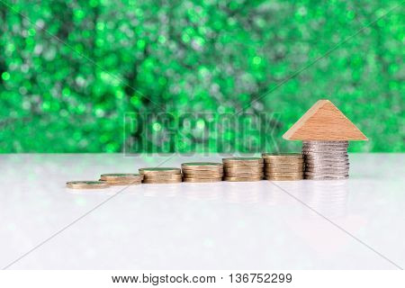 Wooden block houses and coin stacks in a row with a green background