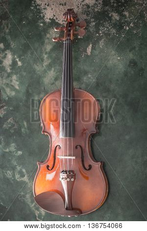 Violin with bow on green cement background