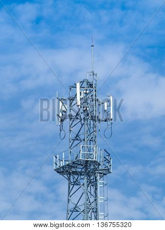 Communication antenna tip with cloud and blue sky.