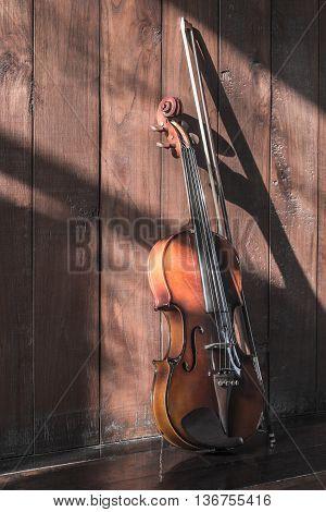 vintage violin on wood background dark tone