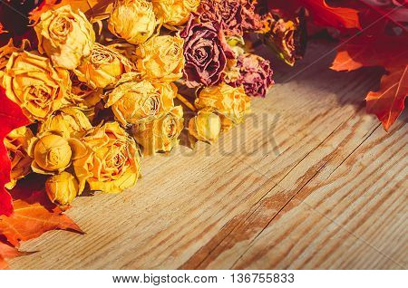Bouquet Of Dried Roses And Autumn Leaves On Wooden Background.