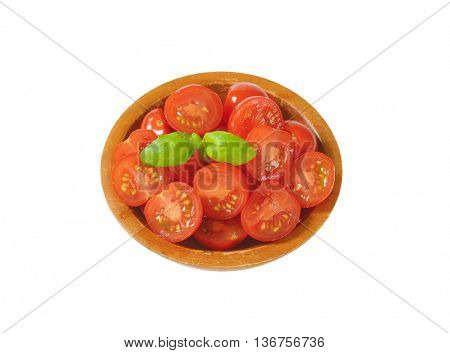 Halved cherry tomatoes in wooden bowl