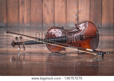 vintage violin with bow on wood background still life