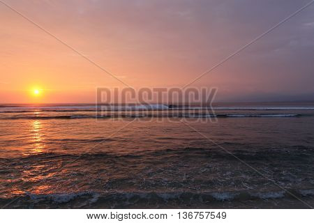 The sunsets across the waves in South Sumatra. This remote area is home to beautiful coastline and surf breaks such as this one south of Krui.