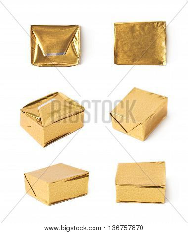 Single bouillon stock broth cube wrapped in golden foil, composition isolated over the white background, set of six different foreshortenings