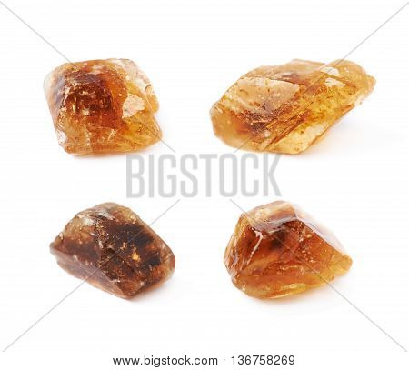 Single large brown rock sugar crystal isolated over the white background, set of four different foreshortenings