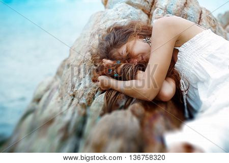 beautiful young woman sleep on the rocks at the beach