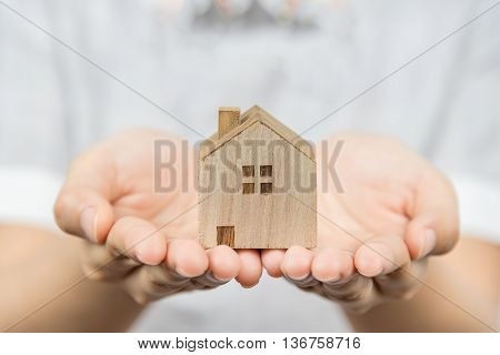 Woman presenting wooden house model in her hand real estate concept.