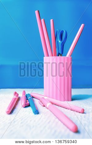 Pink pencil-box with pencils pens and scissors on a blue background.