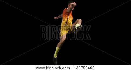 Professional soccer player in blue uniform kicking on training black background