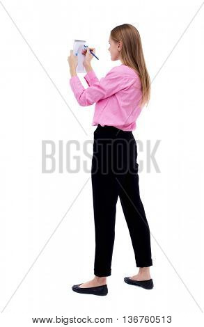 back view of  stands woman takes notes in a notebook. girl  watching. Rear view people collection.   Isolated over white background. Woman office worker in a pink shirt wrote pen in a notebook.